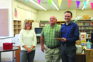 Lori Hunt and Superintendent Bob Dolezal presented Aaron Hansen (right) with a special statue in honor of Hansen's tenure as White Pine Middle School's principal. (Lukas Eggen photo)