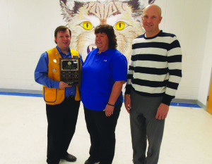 Lions Club President Stephen Bishop presents the revolving plaque to Julie Gonzales, Lions teacher for the month of February while White Pine High School Principal is on hand to congratulate her. (Courtesy photo)