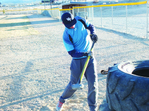 Bobcats pitcher Colton Britton swings a sledgehammer at tires as part of strength conditioning at a baseball practice Tuesday. Garrett Estrada Photo
