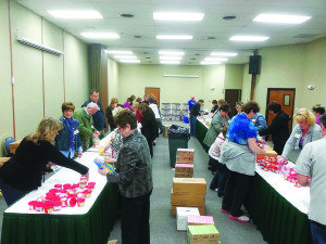 Members of the Heritage Club International were in Ely on March 8 and volunteered their time to help fill over 700 backpacks for the local CACH program at the Bristlecone Convention Center.  Courtesy photo