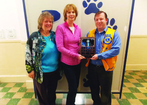 """Ely Lions Club President presents Lisa Petersen with the revolving """"Teacher of the Month"""" plaque while her principal Sheryl Allen is on hand to congratulate her. Courtesy photo"""