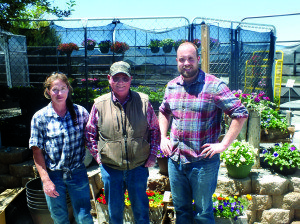 Garrett Estrada Photo Cedar Grove employee Julie Jones stands next to Owner Hal Bybee and his son and Manager Caleb in front of some of their newest flowers.