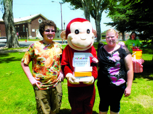 Teresa Stewart Photo Will Hampton (left) and Emily Pringle (right) stand on next to Curious George who is holding the grand prize electronic tablets for the summer reading program.