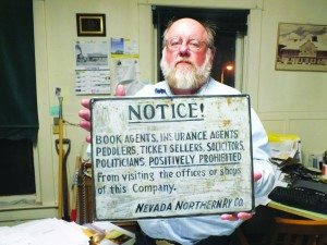 """The Nevada Northern Railway's Executive Director Mark Bassett holds up an old sign that still hangs on the outside walls of the railroad's machine shop, saying """"politicians positively prohibited.""""  (Garrett Estrada photo)"""