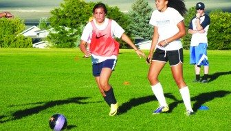 Ladycats coach Tyler Laity watches McKenna Windous battle for a ball during a practice Tuesday.