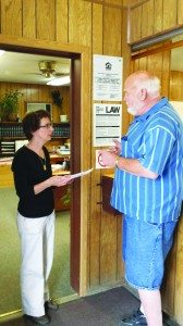 Rick Stork hands over a notice of intent otherwise known as a Recall Petition to Deputy City Clerk Jennifer Lee on Sept. 8. (Courtesy photo)