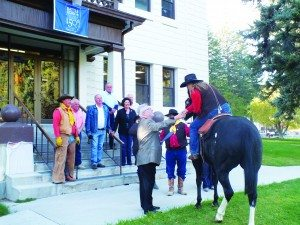 White Pine County Commissioner John Lampros shakes the hand of a Pony Express rider in front of the County Courthouse Thursday morning as part of an event to celebrate Nevada's upcoming 150th anniversary as a state. (Garrett Estrada photo)