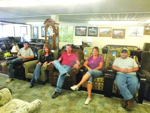 Wilson Bates Furniture Co-Owner Jay Cazier sits with his staff on a selection of his sofas on one of the building's three showroom floors. (Garrett Estrada photo0