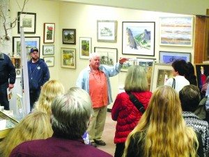 """Art collector Wally Cuchine speaks to a crowd gathered at the Ely Art Bank on Nov. 14 in front of selected pieces from his collection """"Wally's World: The Loneliest Art Collection in Nevada"""" which has been touring the state for over a year. (Garrett Estrada photo)"""
