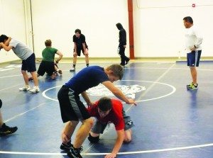Sophomore Monty Moore practices a takedown in a wrestling practice Monday at the Armory. (Garrett Estrada photo)