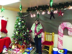 Garnet Mercantile General Manager Mary Howes stands in a specially decorated part of the store where santa will be available to take Christmas pictures on Saturdays for $5. (Garrett Estrada photo)