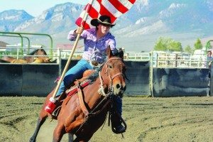 White Pine Rodeo Club member Sadie Leyba carries the flag around the arena at the start of the last year's Nevada State Finals Rodeo in Ely. (Photo courtesy of Western Images)
