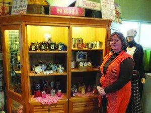 Juliet Noyes, owner of This & That, shows off some of her new, custom Ely stone mugs and candles.  (Garrett Estrada photo)