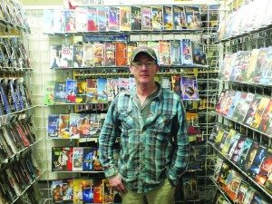 StuffnGo owner Henry Abell stands next to one of his stores many walls of DVD's available for two-day rentals. (Garrett Estrada photo)