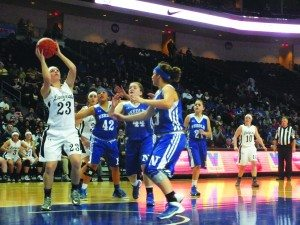 Emily Bischoff drives to the hoop against three Needles players for a layup.