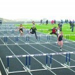 Lily Fullmer leads a 300 meter hurdles race in the rain on White Pine High School's track on Friday. (Garrett Estrada photo)