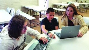 Courtesy photo Learning Bridge Charter School teacher Jamie Lawrence works with two students.
