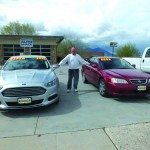 Richard Howe stands between two of the cars for sale at Mike's Auto Shack on Aultman Street. (Garrett Estrada photo)