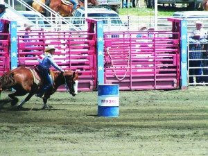 High school contestants pushed their horses to go nearly sideways as they rounded their three barrels during barrel racing.