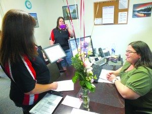 """KDSS radio station hosts Karen Livingston and Jodi Foster surprise Roseanna Toth in her office with prizes after she was selected as the station's May """"Angel in Disguise"""" winner. (Garrett Estrada photo)"""