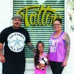 Tattoo artist of over 13 years Danny Herrera stands outside his new tattoo parlor with his wife Teri and daughter Rocklyn. (Garrett Estrada photo)