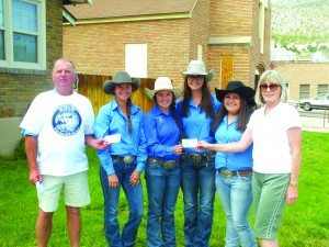 Richard Howe and Leslie Martin of the Kennecott Years All-Class Reunion Committee donate $500 to Jamie Wines, Sadie Leyba, Catherine Odgers and Jesse Leyba of the White Pine Rodeo Club.
