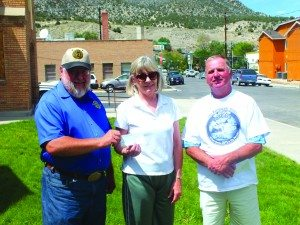 Nevada Northern Railroad Executive Director Mark Bassett  receives a $2,000 donation Leslie Martin and Richard Howe on Aug. 6
