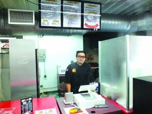 (Garrett Estrada photo) Carlos Moreno stands behind the register at Burrito Farm's new location inside the Silver Sage Travel Center and Truck Stop.
