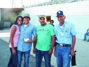 Top jockey of the weekend Uriel Dominguez Jr. is awarded a handmade belt buckle.