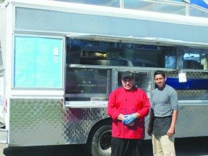 "(Garrett Estrada photo) Felipe Gutierrez and Mario Gonzalez stand in front of the ""Juanita's Tacos"" food truck in the Conoco gas station parking lot."