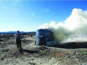 Courtesy photo Eric Roussel of NDF standing with kiln during first phase of burning biomass.
