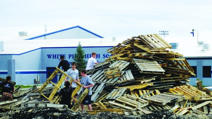 (Garrett Estrada photo) White Pine High School students stack pallets of wood outside of the school in preparation of the annual Homecoming bonfire.