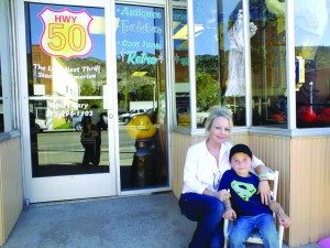 """Cynthia Davis, owner of """"Hwy 50: The Loneliest Thrift Store in America,"""" sits next to her son Christian Trujillo outside her new store in downtown Ely. Hwy 50 sells her collection of antiques, thrift clothing, used furniture and """"retro"""" pieces.  (Garrett Estrada photo)"""