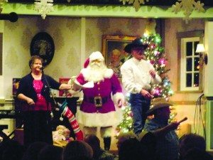 Ross Johnson photo Kathy Tucker, Ed Spear and Santa taking bids from the crowd.