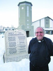 Ross Johnson photo Father McShane endures the elements in front  of the Ten Commandments