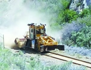 The dustiest job on the railroad is running the ballast regulator. Here it is sweeping the tracks and profiling the roadbed.