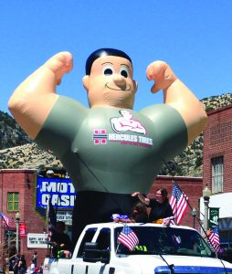 Photo by Marty Bachman  The Hercules Tire man rides high at the annual 4th of July parade.