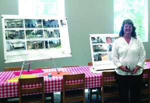 Times photo by Teresa Stewart Lori Romero, director of the White Pine County Library, stands in front of pictures of the library's improvement project.