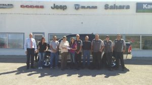 Photo special to the Times/TERESA STEWART  School district personnel accept a check from the staff at Sahara Motors: Adam Young, Maggie Holmes, James Mossow, Susan Jensen, Sandi Greathouse, Brian Pay, Chuck Hutton, Neal Foster, Josh Muir, Frank Craw, (not pictured Raven Hollowbreast)