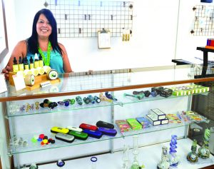 Times photo/Marty Bachman Valerie Vigil stands in front of a display of pipes and other smoking accessories at the Tsaa Nesunkwa headshop at the Silver Sage Travel Center on Great Basin Highway on the Ely Shoshone Indian reservation. The store will begin dispensing medical marijuana to patients in a few months.
