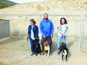 From left, City Councilwoman Pat Robison, Animal Control Officer Bobby Armijo,  Prospector Hotel Office Manager Liz Williams standing with some of the dogs available for adoption